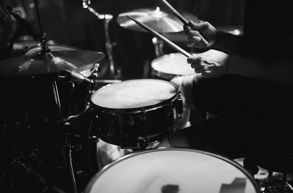 photo of a man using a drum set